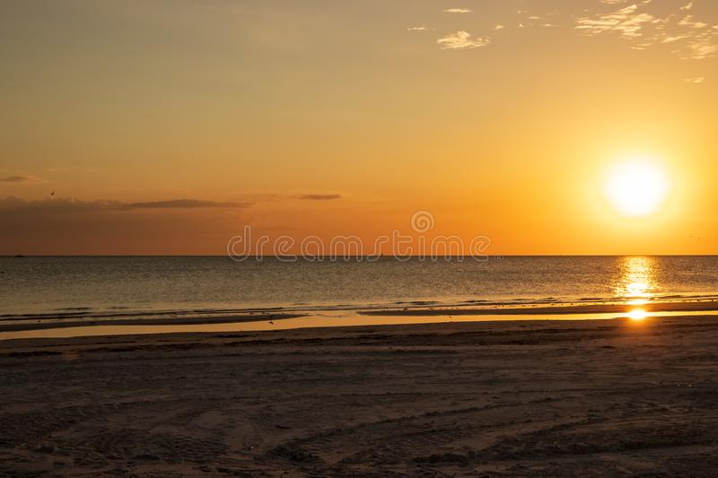 Sunset scene at Fort Myers Beach, FL, with bright orange color, sandpiper silhouette and reflection, and seagulls. Sunset scene at Fort Myers Beach, FL, with royalty free stock image
