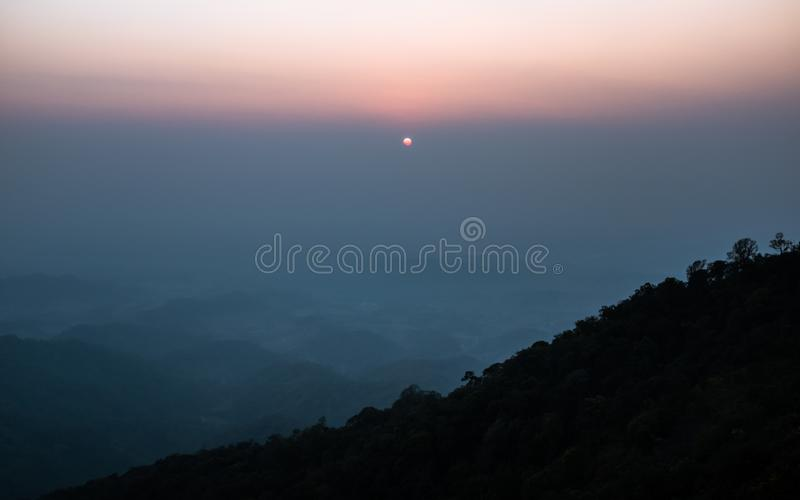 Sunset scene on hight mountain. Sunshine through the clouds. silhouette at the mountain. I. Sunset scene on hight mountain. Sunshine through the clouds royalty free stock photo