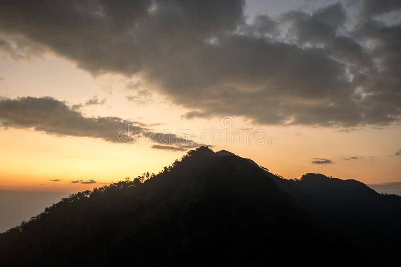 Sunset scene on hight mountain. Sunshine through the clouds. silhouette at the mountain. I. Sunset scene on hight mountain. Sunshine through the clouds royalty free stock photography