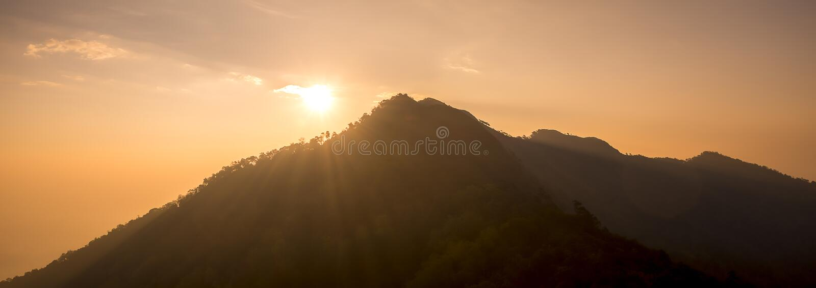 Sunset scene on hight mountain. Sunshine through the clouds. silhouette at the mountain. I. Sunset scene on hight mountain. Sunshine through the clouds royalty free stock images