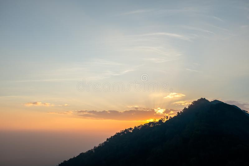 Sunset scene on hight mountain. Sunshine through the clouds. silhouette at the mountain. I. Sunset scene on hight mountain. Sunshine through the clouds stock images