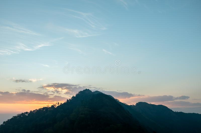 Sunset scene on hight mountain. Sunshine through the clouds. silhouette at the mountain. I. Sunset scene on hight mountain. Sunshine through the clouds royalty free stock image