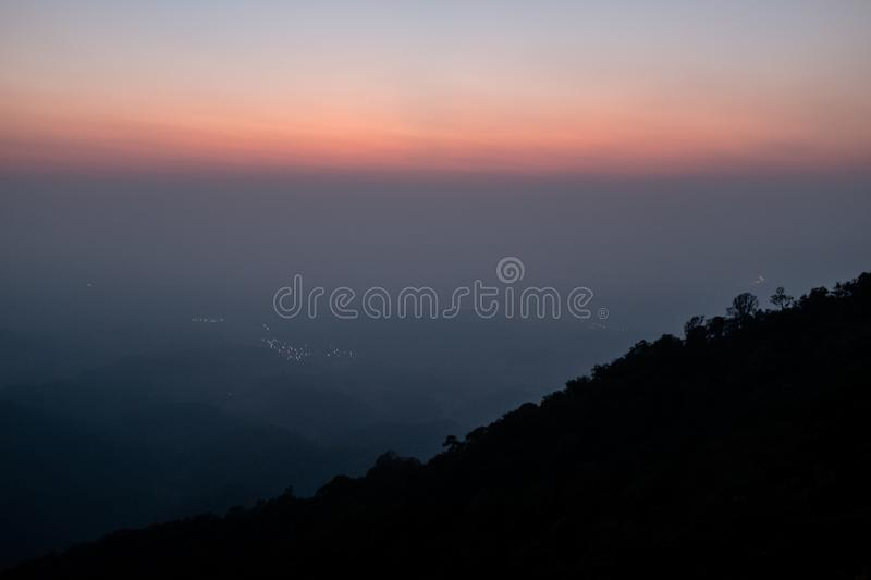 Sunset scene on hight mountain. Sunshine through the clouds. silhouette at the mountain. I. Sunset scene on hight mountain. Sunshine through the clouds stock image