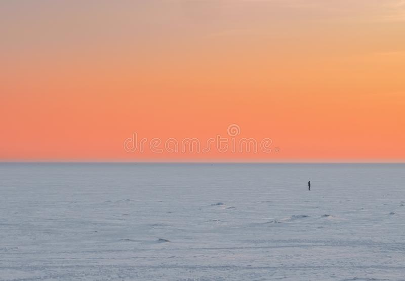 Sunset scene of a lone man figure in the distance in winter on a frozen lake. Minimalism stock photography