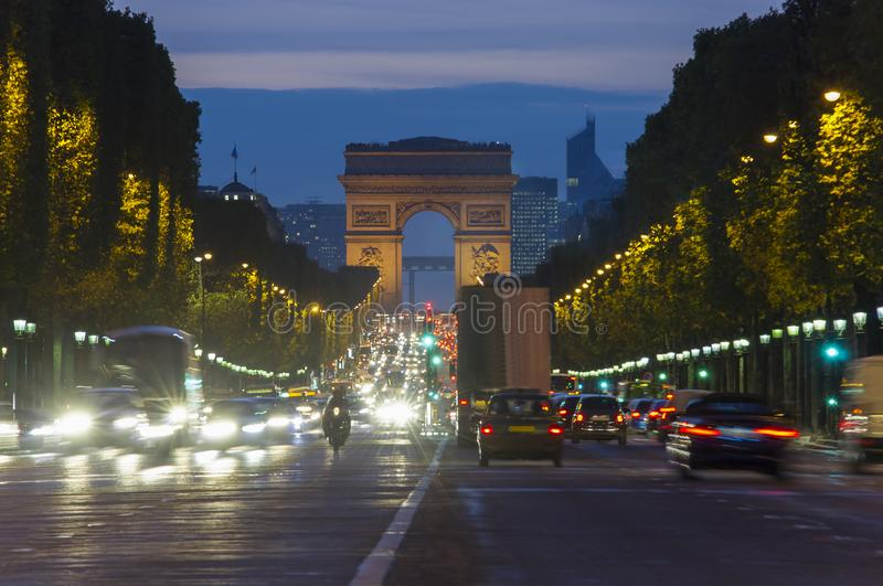 Sunset scene in Paris city. Long exposure photo of street traffic near Arc de Triomphe. Champs Elysees boulevard royalty free stock images