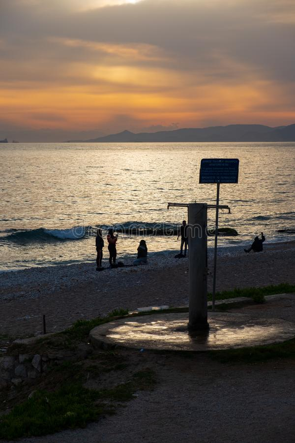 Sunset scene of people silhouettes at Paleo Faliro beach in Athens, Greece stock image