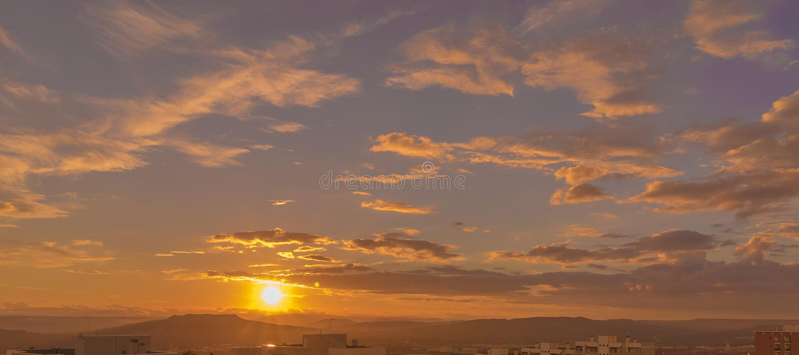 Sunset scene with sun fall behind the clouds and mountains in background, warm colorful sky with soft clouds. Concept of nature stock photos