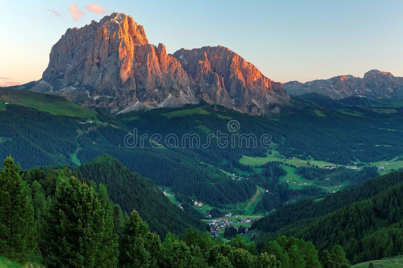 Sunset scenery of rugged Sassolungo-Sassopiatto mountains with alpenglow & a village in green grassy valley. In Col Raiser, Val Gardena, Dolomiti National Park stock image