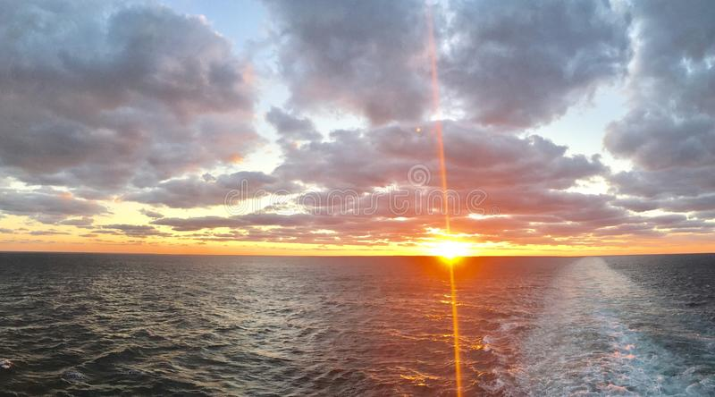 Sunset at sea. Beautiful sunset at sea with a sun going down behind horizon line royalty free stock image