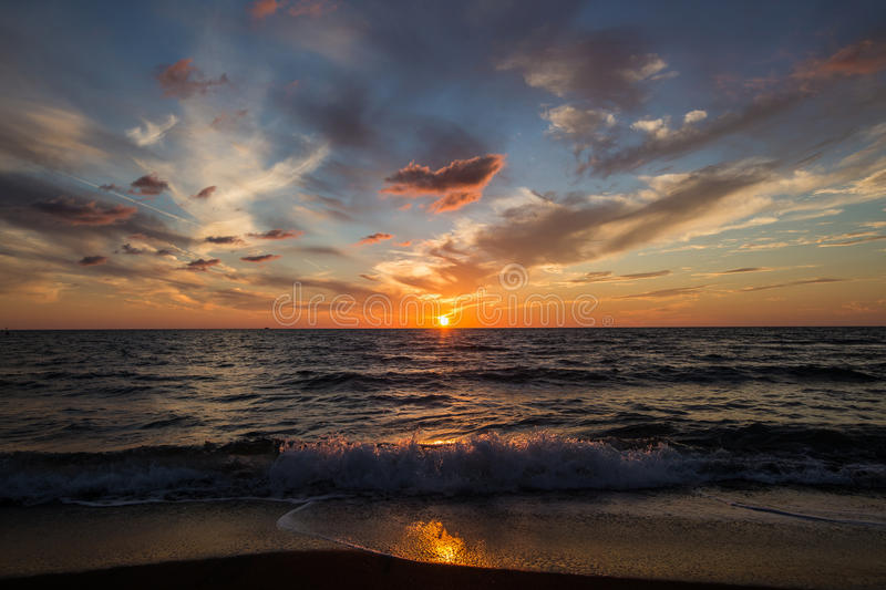 Sunset on sea. Bright sun on sky. Waves royalty free stock images