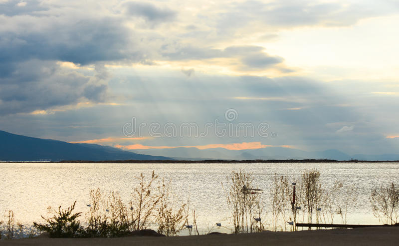 Sunset on the sea with clouds. The sun between clouds. royalty free stock image
