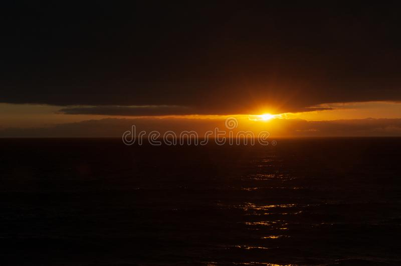 Sunset through the sea and clouds stock photo