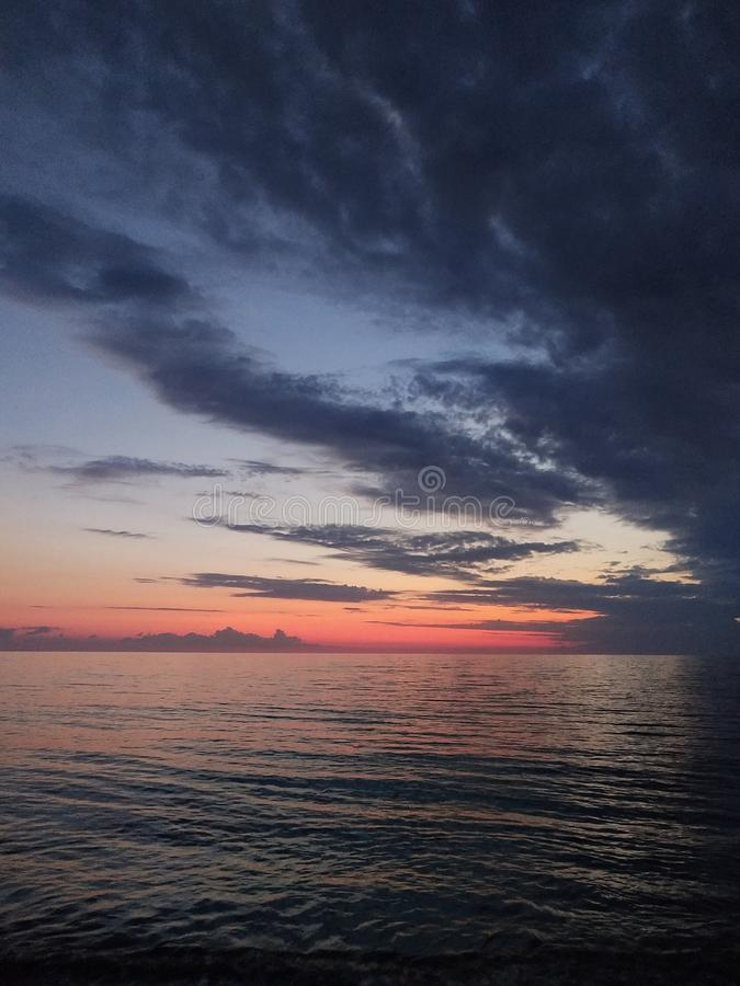 Sunset on the sea coast. Water, sky, skyline, horizon, color, blue, red, clouds, dark, nature stock images