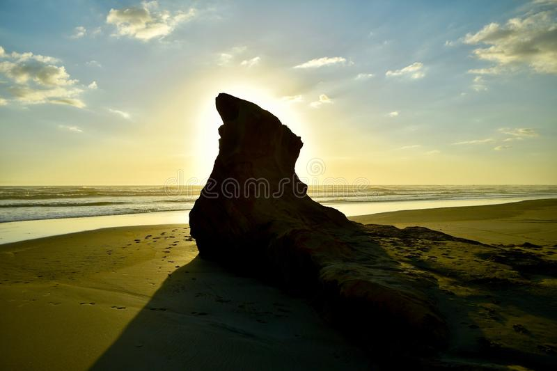 Sunset at the sea shore, with sunlight against a huge rock formation. Dramatic evening sky with black silhouette of the rock. Seascape in the evening; tranquil royalty free stock photos