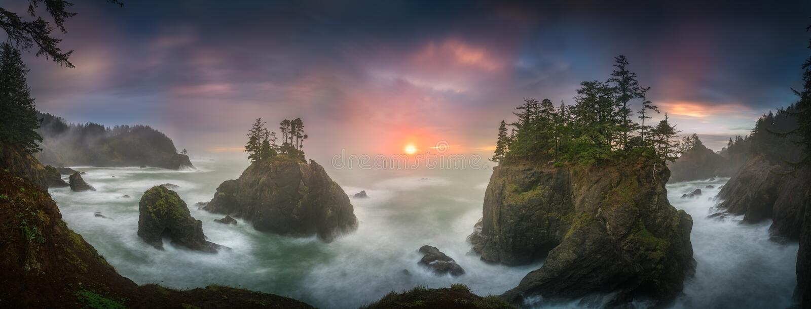 Sunset between Sea stacks with trees of Oregon coast. This is a photograph of big sea stacks with trees of Oregon coast taken at sunset hour stock images