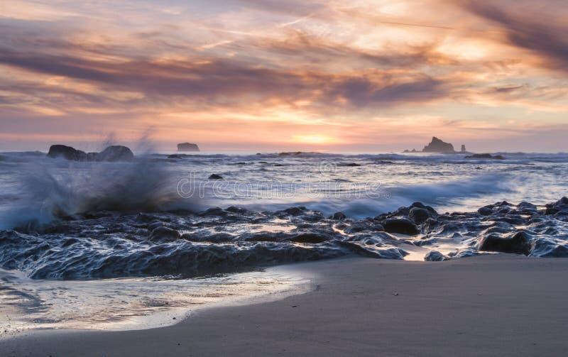Sunset sea stacks and waves Washington state coast Rialto Beach. Beautiful orange and pink sunset and waves crash on rocks at Rialto Beach in Olympic National stock photography