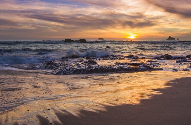 Sunset sea stacks and waves Washington state coast Rialto Beach. Beautiful orange yellow and pink sunset and waves crash on rocks at Rialto Beach in Olympic royalty free stock photos