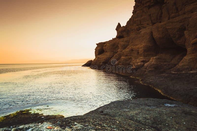 Sunset at the sea. On a stony beach, ocean, sky, sunrise, water, nature, horizon, landscape, background, summer, blue, dawn, rock, dusk, beautiful, orange royalty free stock images