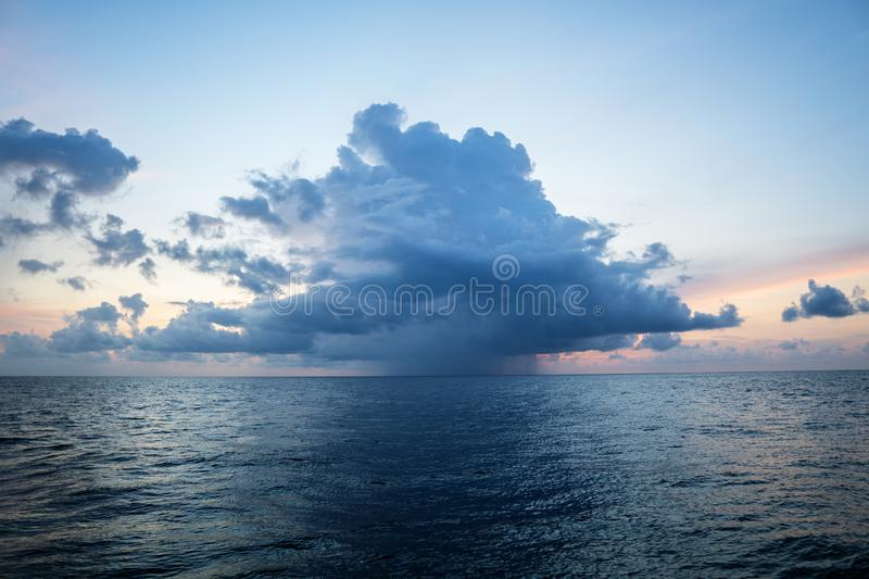 Sunset, sea, the sun is covered with clouds. Open ocean view stock photo