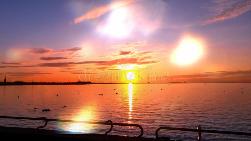 Sunset at sea sun light sky line evening light reflection on sea water gold summer sunset city panorama on horizon  Old town Talli. Nn nature background royalty free stock photos