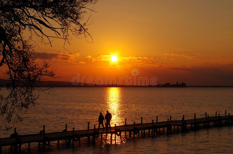 Sunset by the sea. Sundown by the sea or lake. The sun shines through between the clouds and there originates a red light of the dusk. Small waves on the water stock image