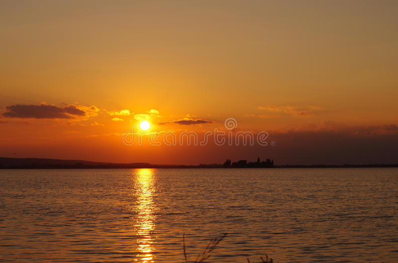 Sunset by the sea. Sundown by the sea or lake. The sun shines through between the clouds and there originates a red light of the dusk. Small waves on the water royalty free stock photos