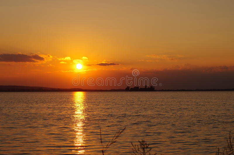 Sunset by the sea. Sundown by the sea or lake. The sun shines through between the clouds and there originates a red light of the dusk. Small waves on the water royalty free stock image