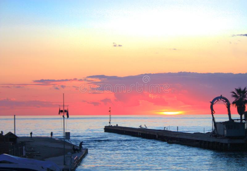 Sunset on the sea view of the harbor. small port immersed in vivid and bright orange and pink colors of sunset or twilight. Spectacular image royalty free stock photos