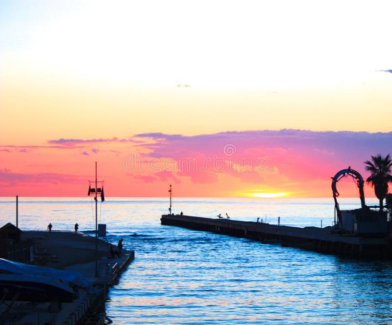 Sunset on the sea view of the harbor. small port immersed in vivid and bright orange and pink colors of sunset or twilight. Spectacular image royalty free stock photography