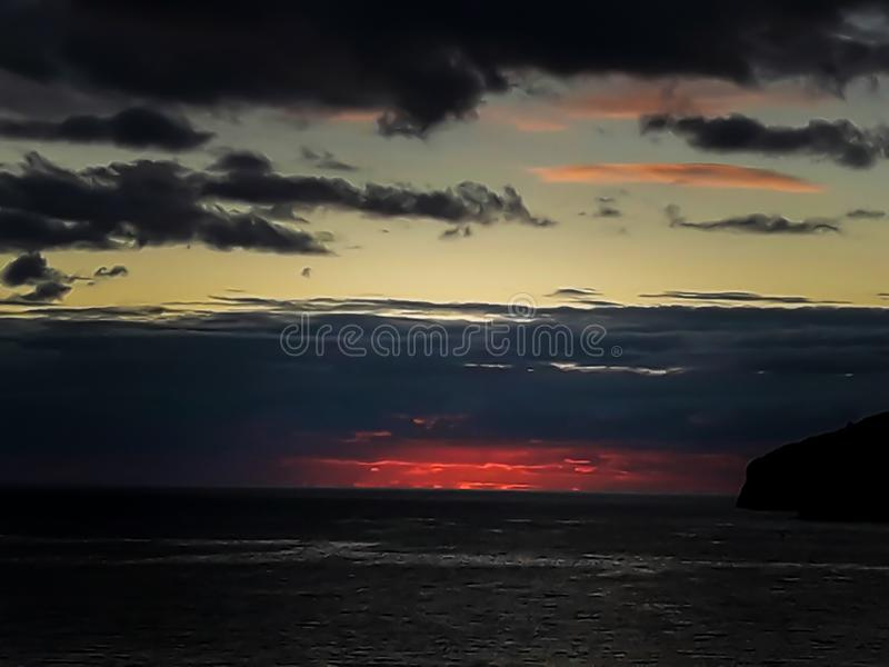 Sunset at the sea with scenic clouds on the horizon. Sunset on the sea with vivid clouds on the horizon of color flow from black to yellow and create the stock images