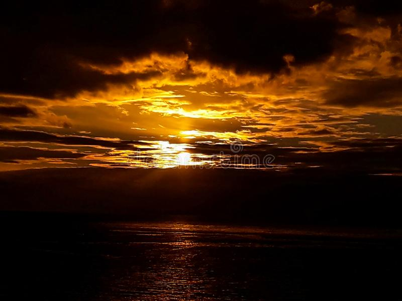 Sunset at the sea with scenic clouds on the horizon. Sunset on the sea with vivid clouds on the horizon of color flow from black to yellow and create the stock photography