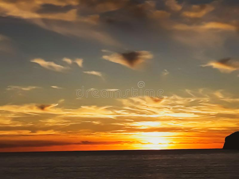 Sunset at the sea with scenic clouds on the horizon. Sunset on the sea with vivid clouds on the horizon of color flow from black to yellow and create the stock image