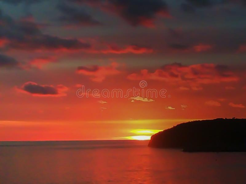 Sunset at the sea with scenic clouds on the horizon. Sunset on the sea with vivid clouds on the horizon of color flow from black to yellow and create the stock photo