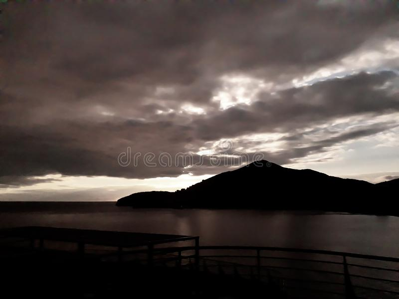 Sunset at the sea with scenic clouds on the horizon. Sunset on the sea with vivid clouds on the horizon of color flow from black to yellow and create the royalty free stock photos