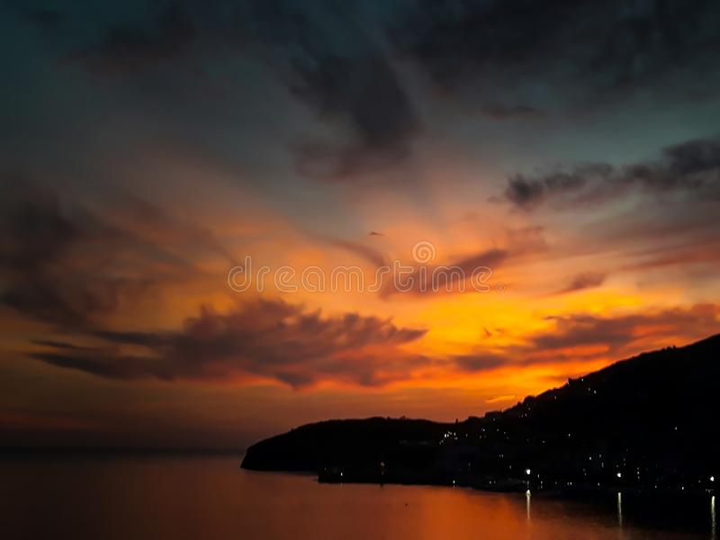 Sunset at the sea with scenic clouds on the horizon. Sunset on the sea with vivid clouds on the horizon of color flow from black to yellow and create the royalty free stock image