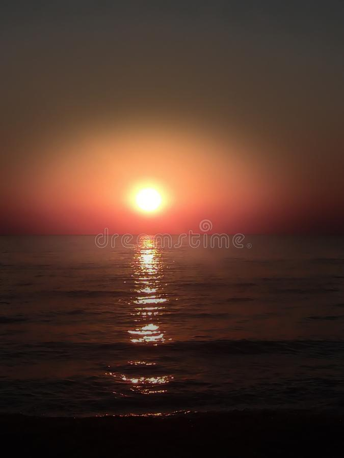 Sunset at the sea with scenic clouds on the horizon. Sunset on the sea with vivid clouds on the horizon of color flow from black to yellow and create the royalty free stock photo