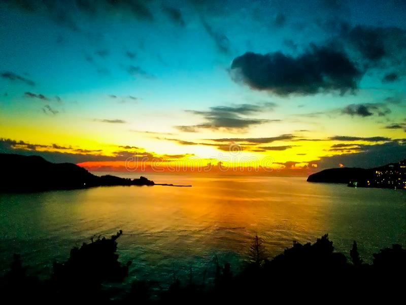 Sunset at the sea with scenic clouds on the horizon. Sunset on the sea with vivid clouds on the horizon of color flow from black to yellow and create the royalty free stock photography