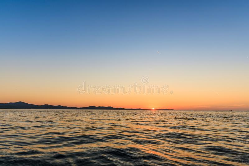 Sunset on the sea from Zadar, Croatia stock photo