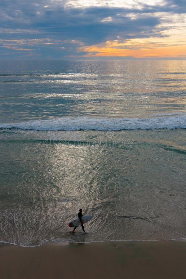 Sunset seascape, orange, blue, yellow sky, with aqua marine green sea, white waves rolling in, surfer at dusk walking in the surf royalty free stock photo