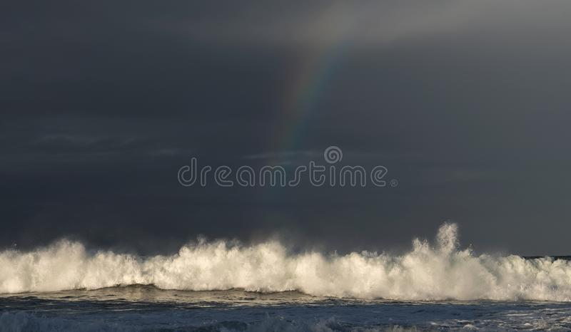 Sunset Seascape. Powerful ocean wave on the surface of the ocean. Wave breaks on a shallow bank. Stormy weather, stormy clouds sky. Background stock photos