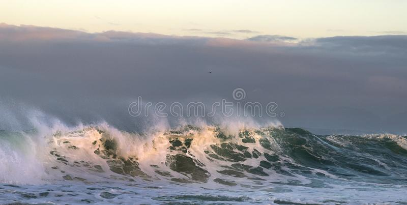 Sunset Seascape. Powerful ocean wave on the surface of the ocean. Wave breaks on a shallow bank. Stormy weather, stormy clouds sky. Background royalty free stock photo