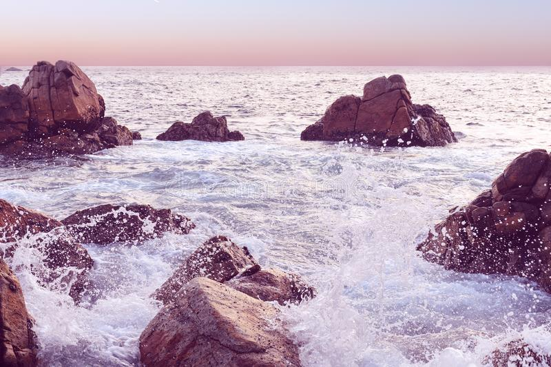 Sunset seascape at Sri Lanka. Wave crashing the rock. Natural background in pink tone. Beautiful evening seascape with sea horizon, clear sunset sky. Rocky stock images