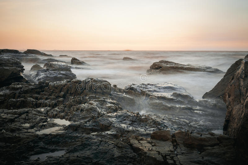 The sunset on the seaside of Do Son. Seascape from a rocky part of Do Son beach near Ba De pagoda on late afternoon stock photo