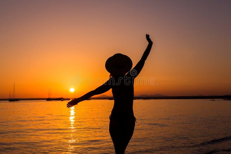 Sunset, sexy woman silhouette. Carefree woman enjoying the sunset on the beach. Happy lifestyle. Mallorca. Es Prenc beach. royalty free stock photos