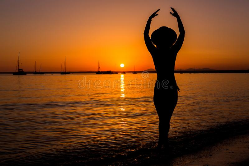 Sunset, sexy woman silhouette. Carefree woman enjoying the sunset on the beach. Happy lifestyle. Mallorca. Es Prenc beach. royalty free stock photography