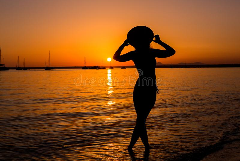Sunset, sexy woman silhouette. Carefree woman enjoying the sunset on the beach. Happy lifestyle. Mallorca. Es Prenc beach. royalty free stock image
