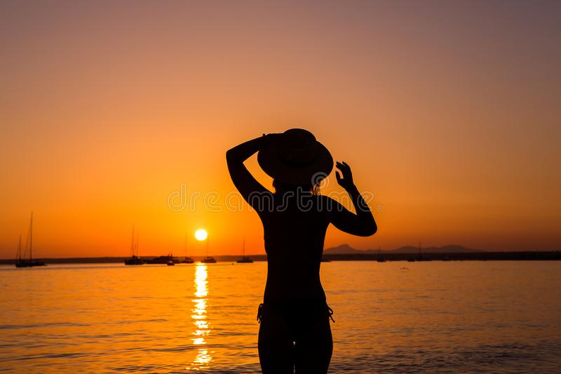 Sunset, sexy woman silhouette. Carefree woman enjoying the sunset on the beach. Happy lifestyle. Mallorca. Es Prenc beach. stock images