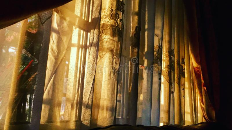Sunset shining through the curtains stock images