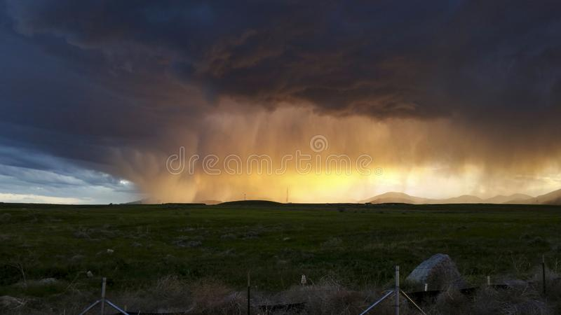 Sunset shining through a summer storm over the Oquirrh Mountains stock photography