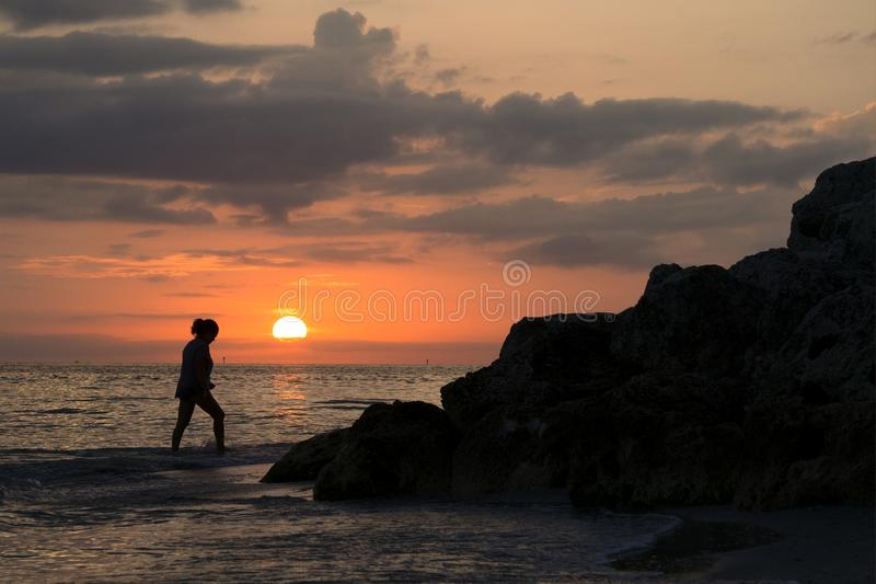 Sunset and shlhouette of a woman on the Gulf of Mexico near St. Pete Beach, Florida. Beautiful photo of a sunset with the silhouette of a woman walking through stock photo